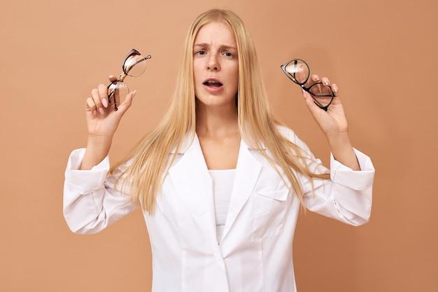 Нерешительная красивая молодая женщина-покупательница в очках с сомнительным выражением лица Бесплатные Фотографии