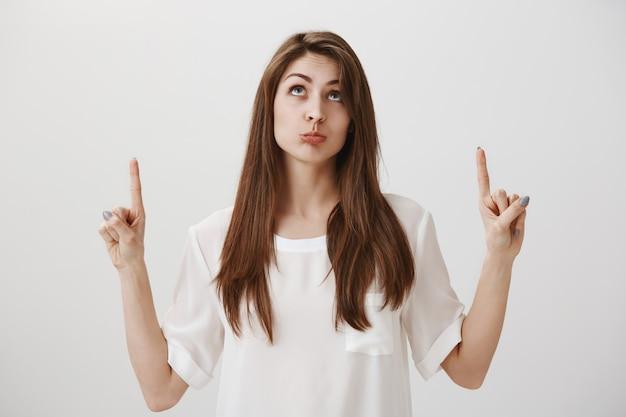 Нерешительная надутая девушка, указывая пальцами вверх, думая Бесплатные Фотографии