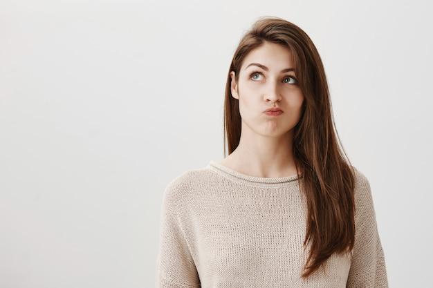 Нерешительная задумчивая девушка принимает решение, нерешительно смотрит в левый верхний угол Бесплатные Фотографии
