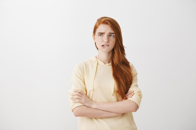 Indecisive worried redhead girl biting lip and looking left concerned Free Photo
