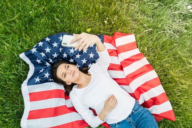 Концепция дня независимости с женщиной, берущей себя на американский флаг Бесплатные Фотографии