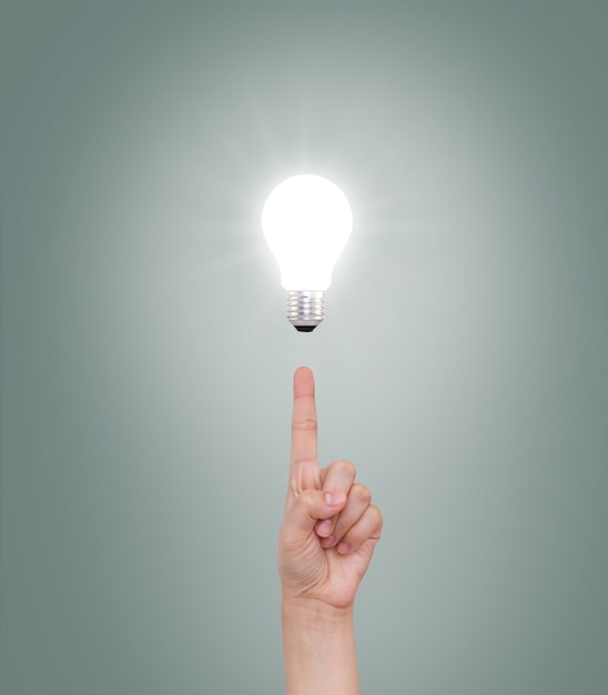 Index finger pointing at an illuminated bulb Free Photo