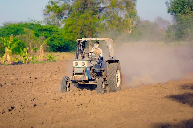 경운기로 파종하기 위해 트랙터를 준비하는 트랙터가있는 인도 / 아시아 농부, 인도 농업 현장 프리미엄 사진