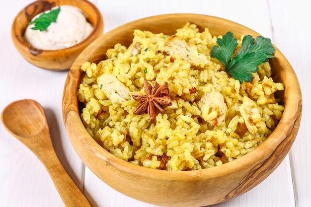 Индийские бирьяни с курицей, йогурт, специи пластины на деревянном столе. новогоднее, рождественское блюдо. Premium Фотографии