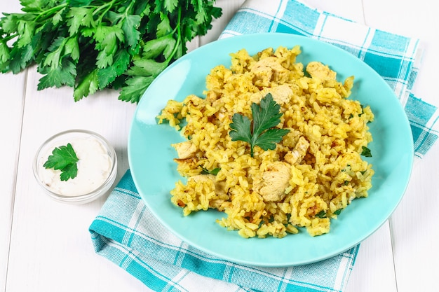 Indian biryani with chicken, yogurt and spices in a plate on wooden table. new year, christmas dish Premium Photo