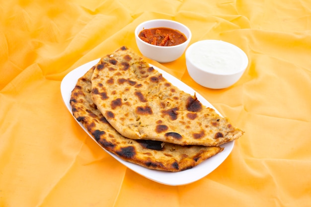 Indian breakfast dish aloo paratha served with curd and pickle Premium Photo