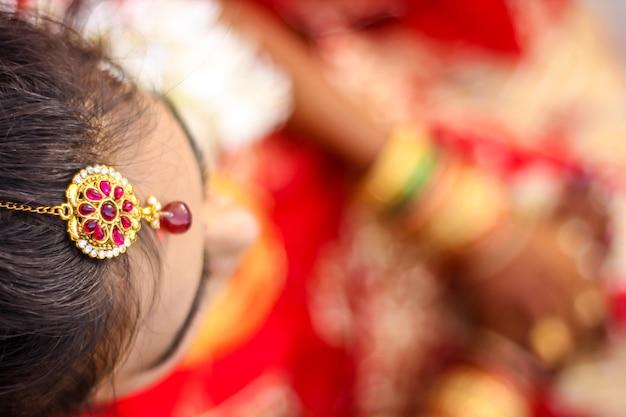 インドのブライダルを示すウェディングヘアスタイルとヘッドジュエリー Premium写真
