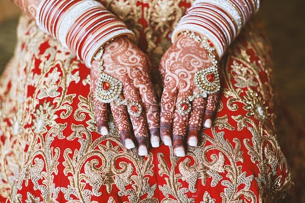 Indian bride's hand with menhdi (henna) tattoo and  bangles on her wrist Premium Photo