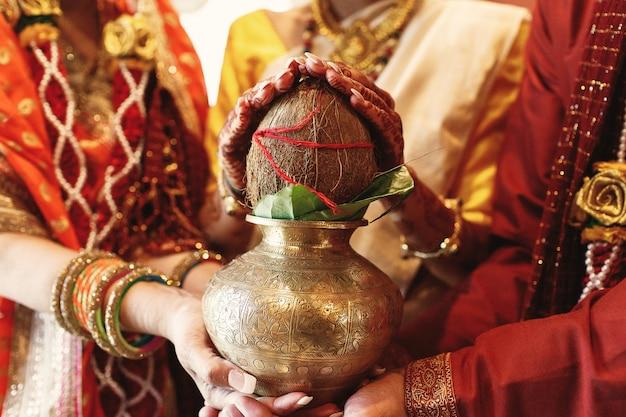 인도 신부의 부모는 그녀의 손에서 코코넛 그릇을 개최 무료 사진
