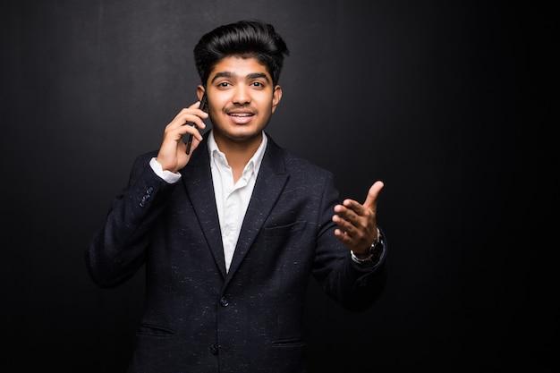 Uomo indiano di affari che parla sul telefono sulla parete nera Foto Gratuite