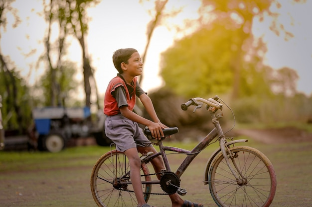 Indian child on bicycle, playing in outdoor Premium Photo