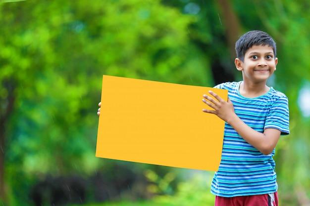 Indian child holding empty poster Premium Photo