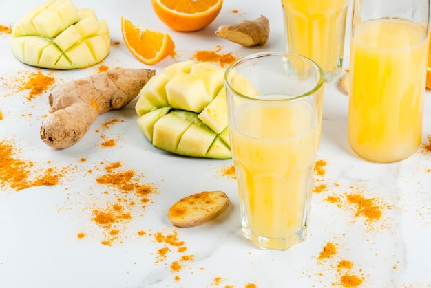 Indian cuisine recipes. healthy food, detox water. traditional indian mango, orange, turmeric and ginger smoothie, on a white marble table. copy space Premium Photo