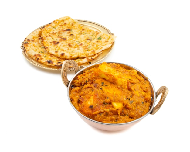 Indian cuisine sweet and spicy paneer pasanda served with garlic naan on white background Premium Photo