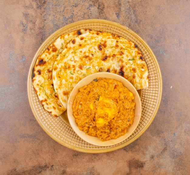 Indian cuisine sweet and spicy paneer pasanda served with garlic nan Premium Photo