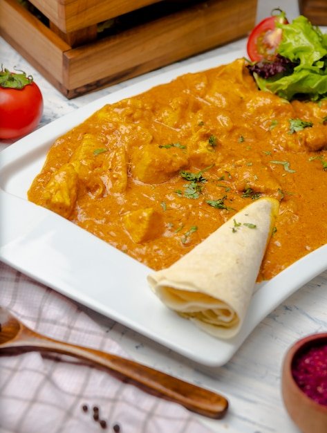 Indian curry with chicken breast and tomato sauce served with lavash. Free Photo