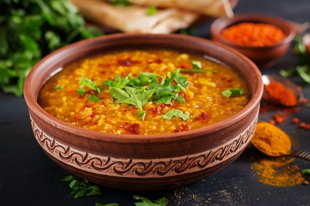 Indian dhal spicy curry in bowl, spices, herbs, rustic black wooden background. Premium Photo