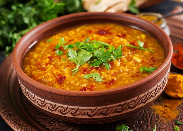 Indian dhal spicy curry in bowl, spices, herbs, rustic black wooden table Free Photo
