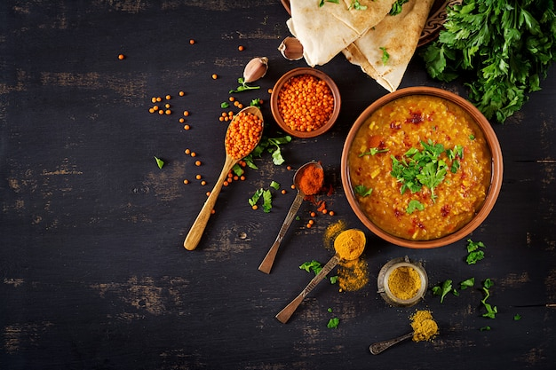 Индийский dhal пряный карри в миску, специи, травы, деревенский черный деревянный фон. Premium Фотографии