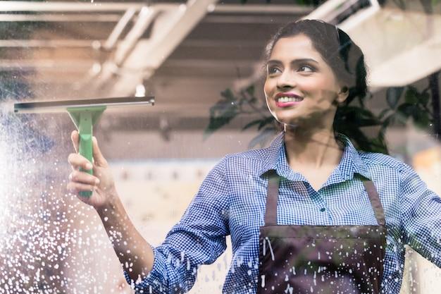 Indian employee cleaning windows Premium Photo