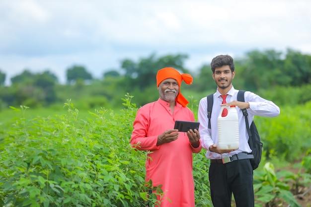 畑で肥料瓶を見せているインドの農民と農学者 Premium写真