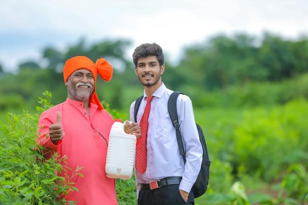 農学者が畑にいるインドの農民、農学者と農学者が肥料の瓶を見せている Premium写真