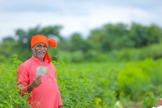 お金とタブレットを持つインドの農民 Premium写真