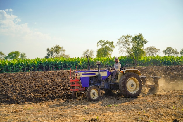 Indian farmer with tractor preparing land for sowing with cultivator Premium Photo