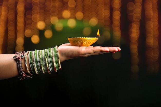 Indian festival diwali, lamp in hand Premium Photo