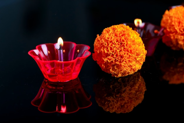 Indian festival diwali ,marigold flower and colorful lamps of oil on black Premium Photo