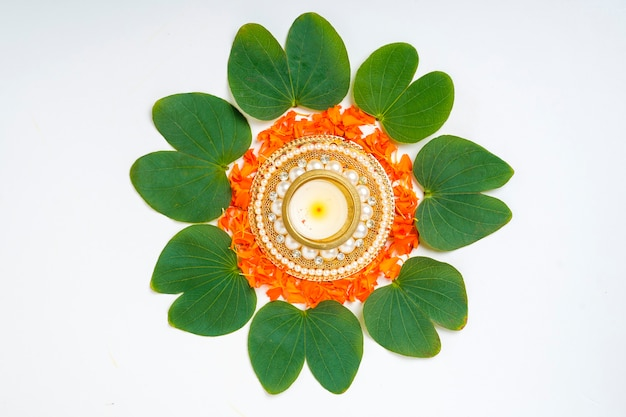 Indian festival dussehra compostion with green leaf ,flowers and lamp Premium Photo