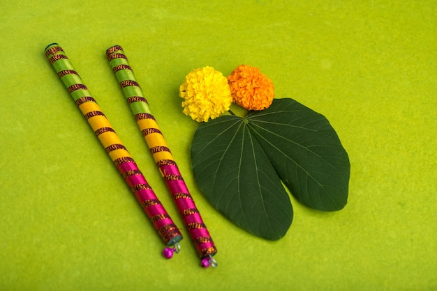 Indian festival dussehra and navratri, showing golden leaf (bauhinia racemosa) and marigold flowers with dandiya sticks on a green background Premium Photo