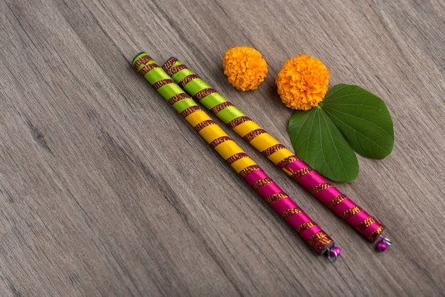 Indian festival dussehra and navratri, showing golden leaf (bauhinia racemosa) and marigold flowers with dandiya sticks on a wooden background Premium Photo