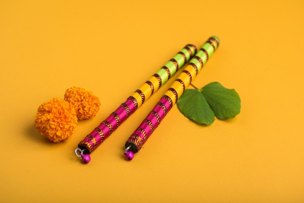 Indian festival dussehra and navratri, showing golden leaf (bauhinia racemosa) and marigold flowers with dandiya sticks. Premium Photo