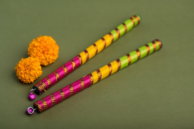Indian festival dussehra and navratri with marigold flowers and dandiya sticks Premium Photo