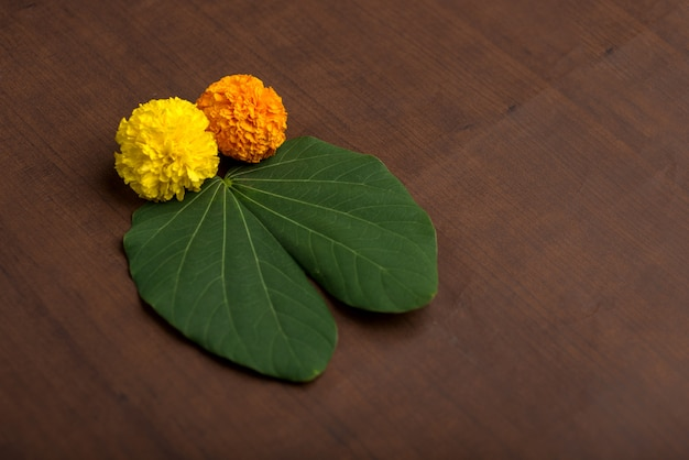 Indian festival dussehra, showing golden leaf (bauhinia racemosa) and marigold flowers on a brown background. Premium Photo