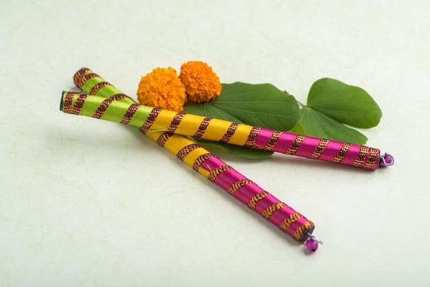 Indian festival dussehra, showing golden leaf (bauhinia racemosa) and marigold flowers with dandiya sticks. Premium Photo
