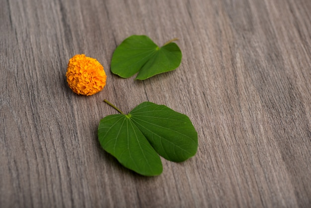 Indian festival dussehra, showing golden leaf (bauhinia racemosa) and marigold flowers on a wooden background. Premium Photo