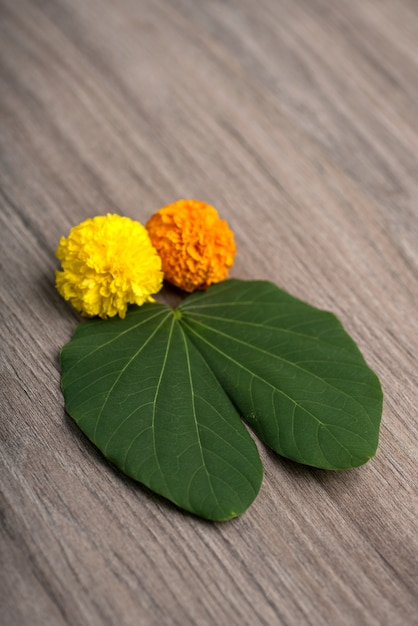 Indian festival dussehra, showing golden leaf (bauhinia racemosa) and marigold flowers on a wooden table. Premium Photo