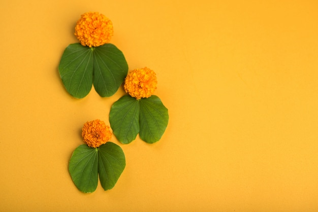 Indian festival dussehra, showing golden leaf (bauhinia racemosa) and marigold flowers on a yellow background. Premium Photo