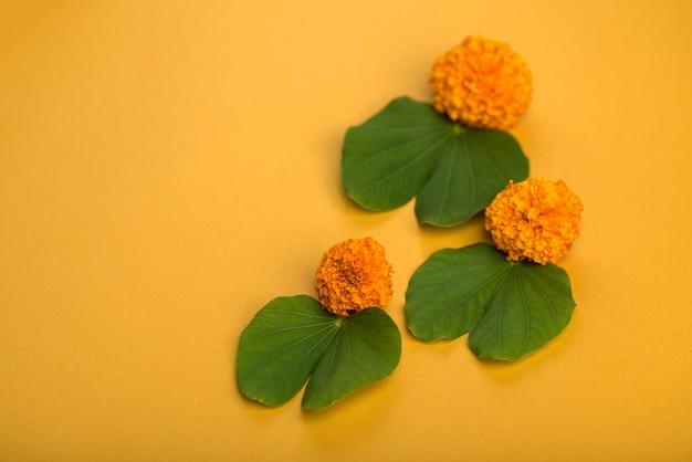 Indian festival dussehra, showing golden leaf (bauhinia racemosa) and marigold flowers. Premium Photo