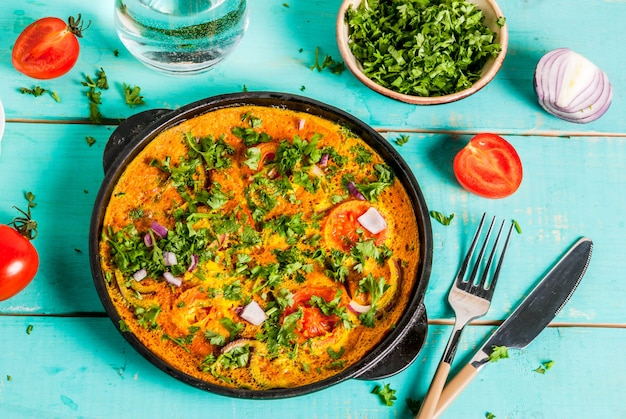 Indian food recipes, indian masala egg omelet, with fresh vegetables - tomato, hot chili pepper, parsley, light blue wooden , copyspace Premium Photo