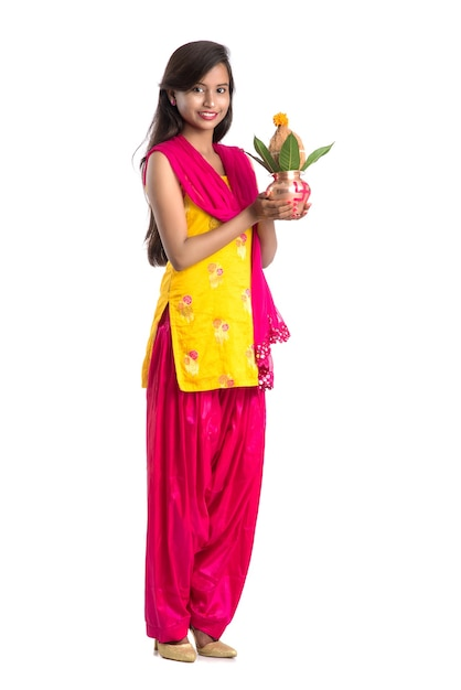 Indian girl holding a traditional copper kalash, indian festival, copper kalash with coconut and mango leaf with floral decoration, essential in hindu pooja. Premium Photo
