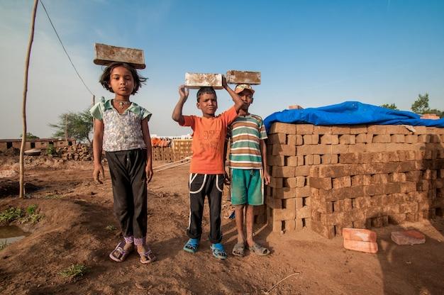 レンガ窯や工場で手作業で伝統的なレンガを作るのを手伝う労働者のインドの子供たち Premium写真