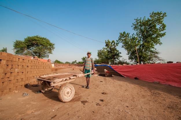 レンガ工場で伝統的なレンガで作るのを助ける労働者のインドの子供たち Premium写真