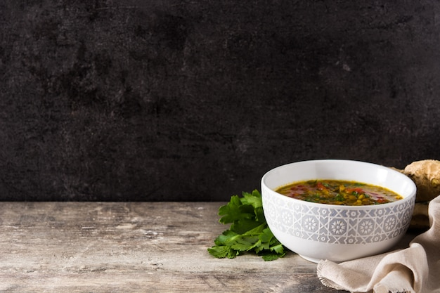 Indian lentil soup dal (dhal) in a bowl on wooden table. copy space Premium Photo