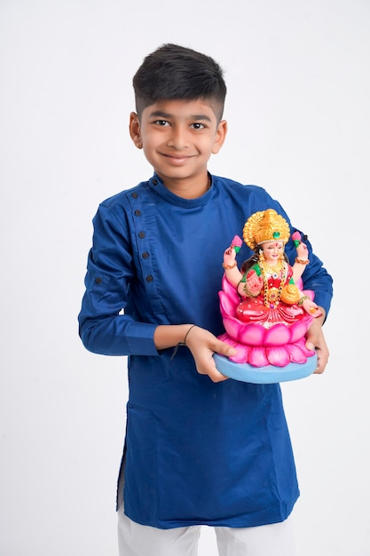 Indian little boy in ethnic wear and holding laxmi sculpture in hand Premium Photo