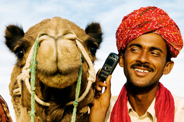 Indian man and camel on the phone, rajasthan, india. Premium Photo