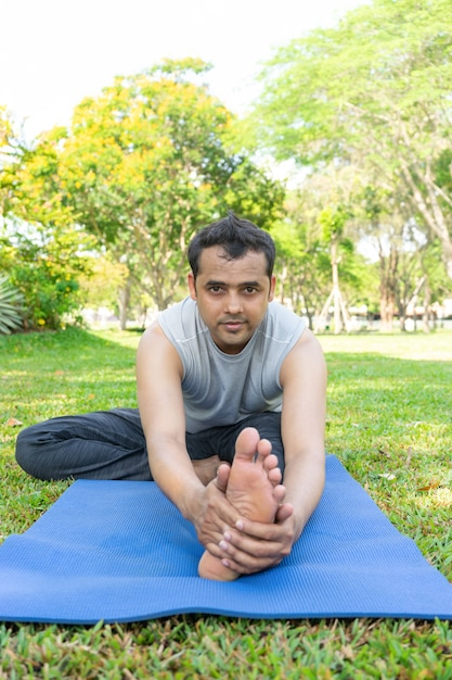 Download This Free Photo Indian Man Doing Head To Knee Forward Bend Outdoors On Mat In Park With Trees