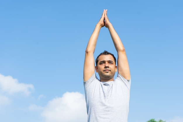 Indian man doing yoga and pressing hands together above head outdoors Free Photo